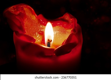 red candle with flame and melting wax against a dark background with bokeh, could be used for christmas, birthday, advent or new year, but also for mourning, death and hope