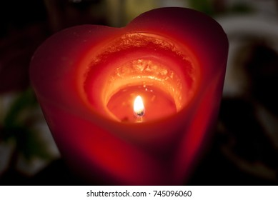 A red candle in the form of a heart burns