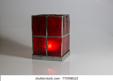 red candle glass with flaming candle in christmas and romantic times