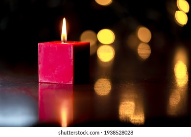 Red candle on dark background with bokeh Christmas lights. Christmas card motive.