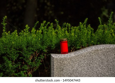 Red candle on a gravestone