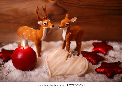 a red candle with two bambis in the snow and wooden background