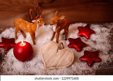 a red candle with two bambis in the snow and wooden background photagraphed from above