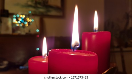Red candles of different sizes. Candlelight flames on burning wickes closeup. Glowing fire of red candlesticks in darkness. Christmas candles closeup with blurred Christmas lights on background