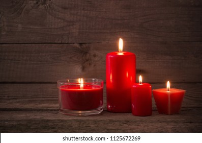 red candles on dark wooden background