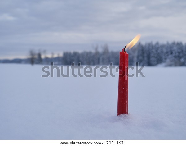 red candles on white snow background outside in winter
