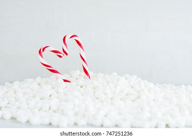 Red candy canes heart in pile of marshmallow