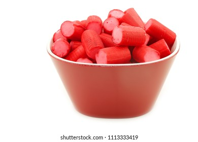 Red candy with pink filling in a red bowl on a white background