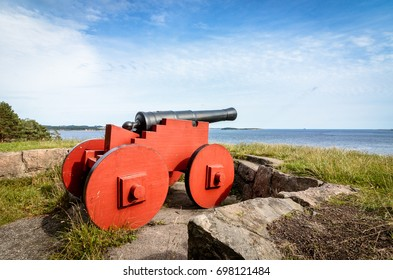 Red cannon standing at Odderoya, Kristiansand, Norway. View to the sea, blue sky