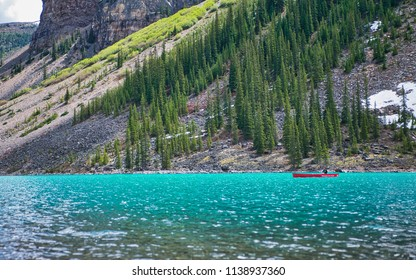 Red canoe on blue lake Moraine. Peace and quiet place.