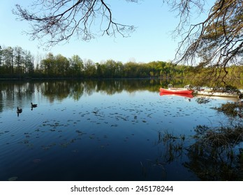 Red canoe and peaceful lake in the morning calm, near Stratford, Ontario, Canada
