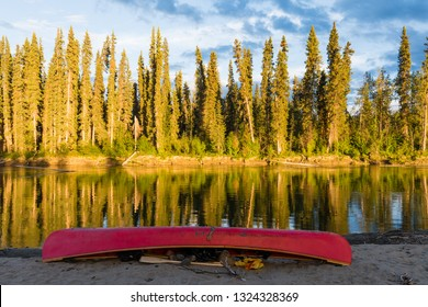 Red canoe turned over on shore of Nisutlin River, Yukon Territory, Canada, on a beautiful summer evening in boreal forest taiga