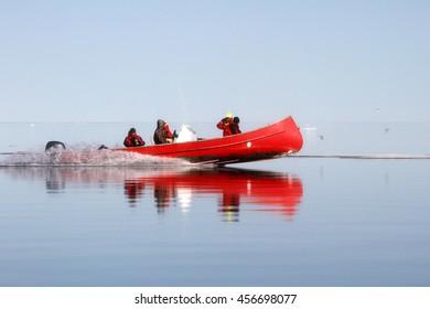 Red canoe or Zodiac in Arctic Ocean