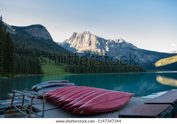 Red canoes are aligned on the boat launching area of Emerald Lake