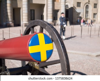 Red canon with Swedish flag against Swedish Royal guard