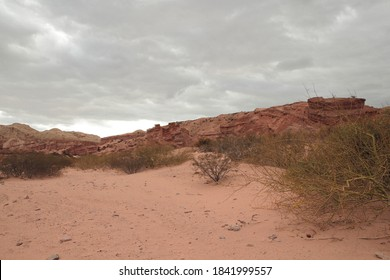 Red canyon. View of the arid desert, red sand, shrubs bushes, sandstone and rocky formation under a cloudy sky.
