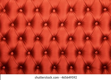 Red capitone textile background, retro Chesterfield style checkered soft tufted fabric furniture diamond pattern decoration with buttons, close up