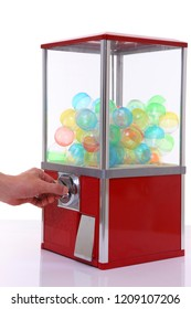 red capsule toy vending machine with hand turn a lever on white background
