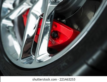 Red Car Brakes Closeup and Chromed Alloy Wheel. Low Profile Sport Tire