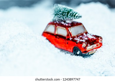 The red car carries along on the snow snowdrifts Cristmas tree