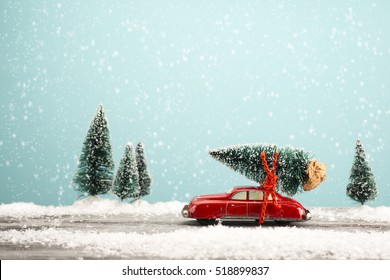 Red car carrying a Christmas tree in a snowy landscape. Space for text.
