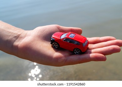 red car in a child's hand against the sea, a summer's day holiday and car children