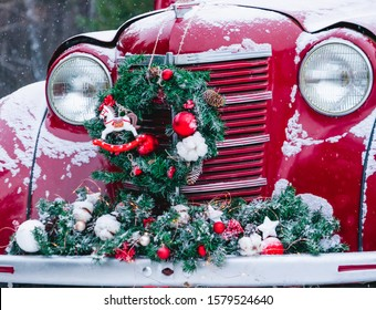 A red car with Christmas decorations and Christmas tree is standing in a snowy winter forest. Festive New Year concept.