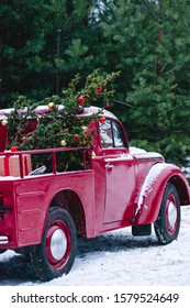 A red car with Christmas decorations and a Christmas tree is standing in a winter forest. Festive New Year concept.