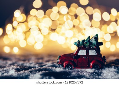 Red car with a Christmas tree driving through snowy road. Fairy lights, wintertime.