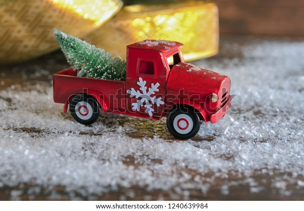 Red car, decorated with snowflake, carrying  a Christmas fir tree on the snow background  for  celebrated Merry Christmas.