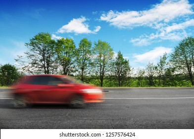 A red car driving fast on the  countryside road with green trees and bushes against a blue sky with clouds, blur