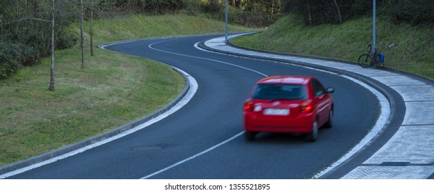 Red car driving fast on the curve of road