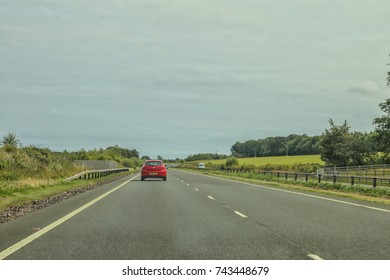 Red car driving on the left side of a quiet motorway