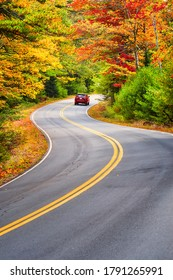 A red car driving through winding road with beautiful autumn foliage trees in New England.