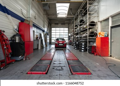 Red car during overhaul in a modern garage with a lift
