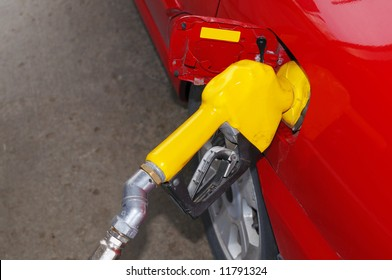 Red car filling up at a gas station