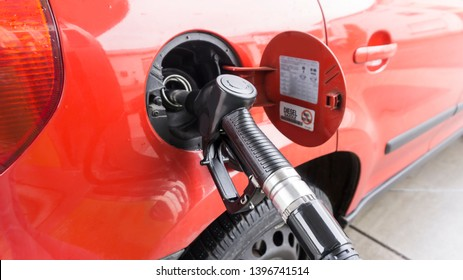 A red car is at a gas station and is fueled with diesel. Closeup of the tap and the tank.