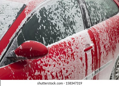 red car getting a wash with soap