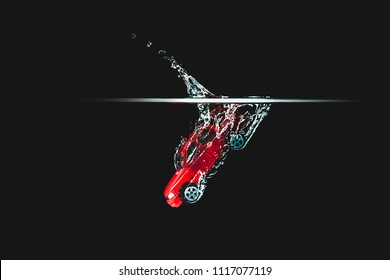 A red car hits the water, black background. Toy car, vehicle dropping in water and creating a splash. Toy thrown into the water, road accident, the effect of the car's fall.