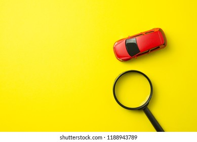 Red car and magnifying glass on yellow background with copy space. Auto insurance business concept. Check car insurance quote for get the best deal. Cover life, property damage, injury of third party