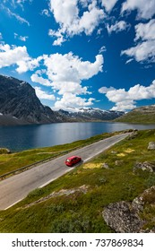 Red car in mountains of Norway, Europe. Auto travel through scandinavia. Blue cloudy sky and lake in background.
