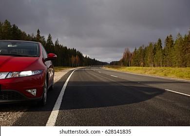 Red car on asphalt road for traveling.