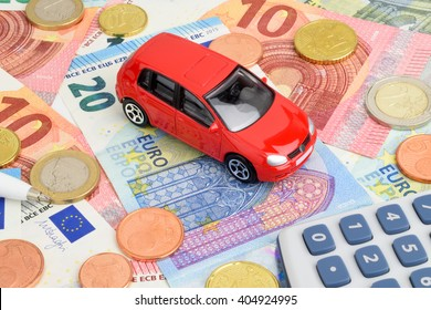 A red car on Euro currency notes and coins, representing car finance.