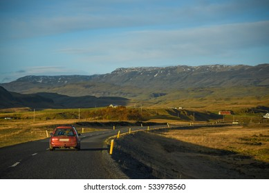 red car on the long asphalt road among beautiful scenic landscape and blue sky in summer of Iceland