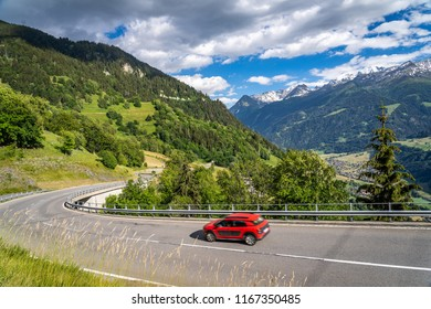 Red car on a road through switzerland alps. Curvy road in mountains. Traveling concept background.