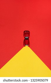 Red car is on red and yellow abstract  background with reflector on the road. Abstract conception.