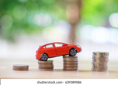 Red car over a lot of stacked coins. car insurance concept