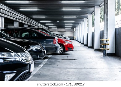 Red car paked in underground garage with lots of vehicles