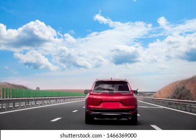 The red car is racing along a straight road against the background of a golden field and a blue sky. Travelling by car.