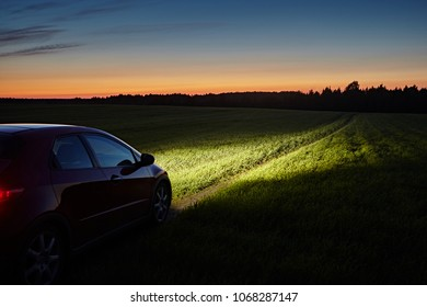 A red car rides along a road and fields in the countryside. The lights from the headlights are on. Landscape with the sky in the background of the white night at summer